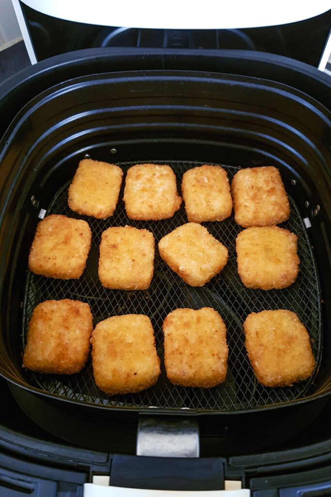 Air fried mac and cheese bites in air fryer basket.