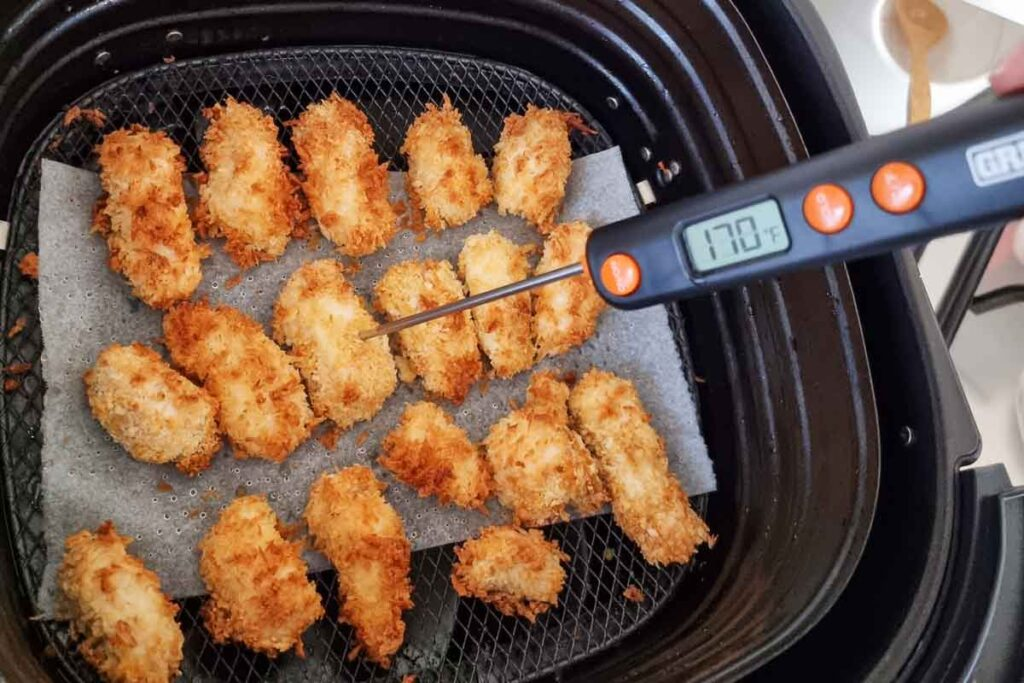 Air fried popcorn chicken being tested with a meat thermometer - temp shows 170F.