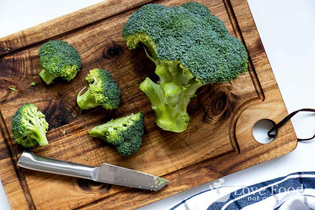 Broccoli being cut into florets on a wooden board.