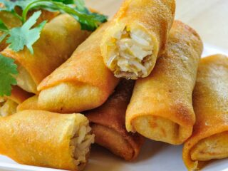 A pile of egg rolls on a white plate.