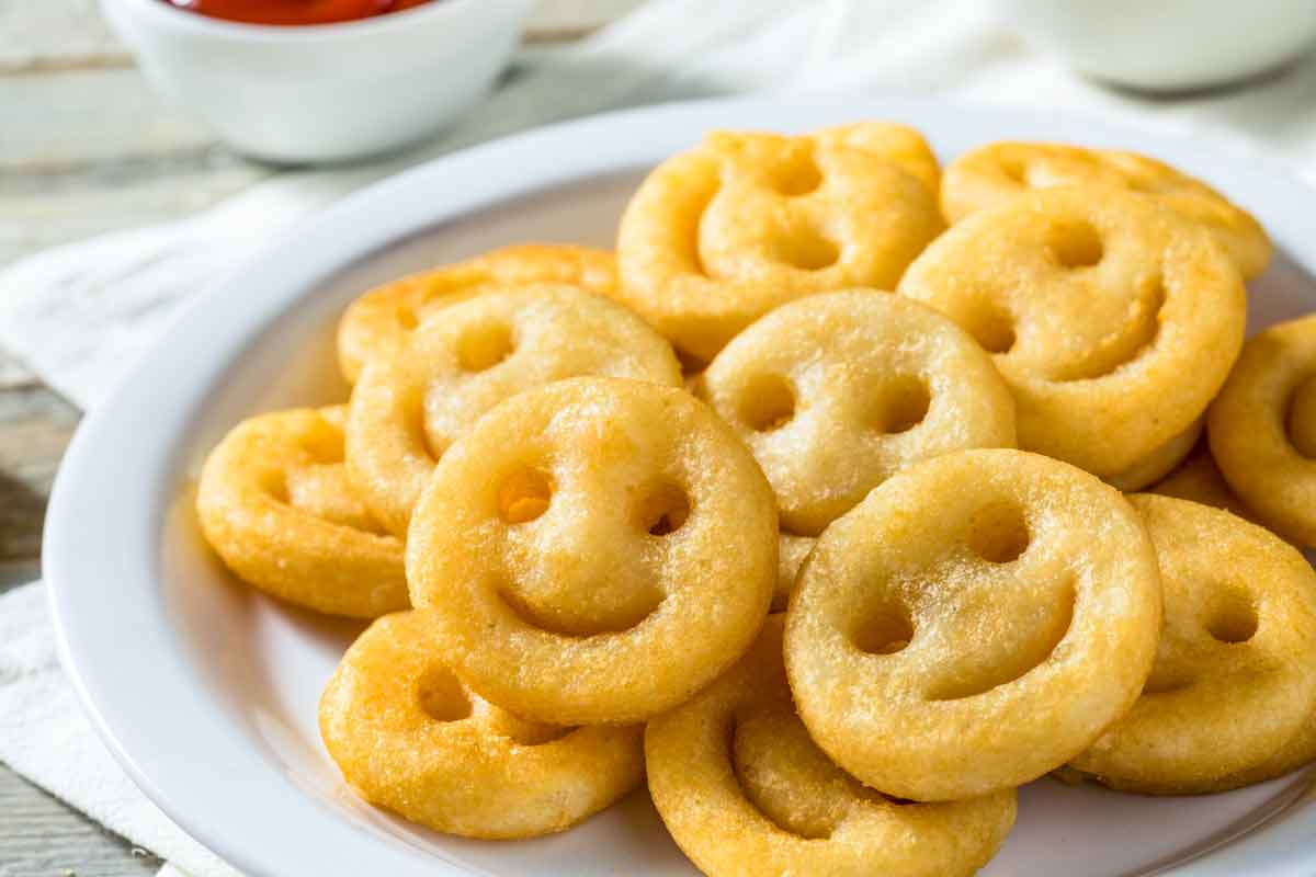 Golden brown smiley fries on a white plate.
