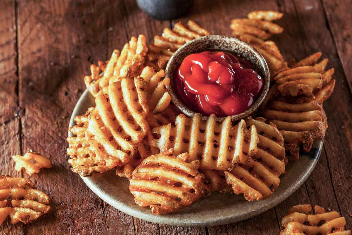 Waffle fries on a white plate with tomato sauce.