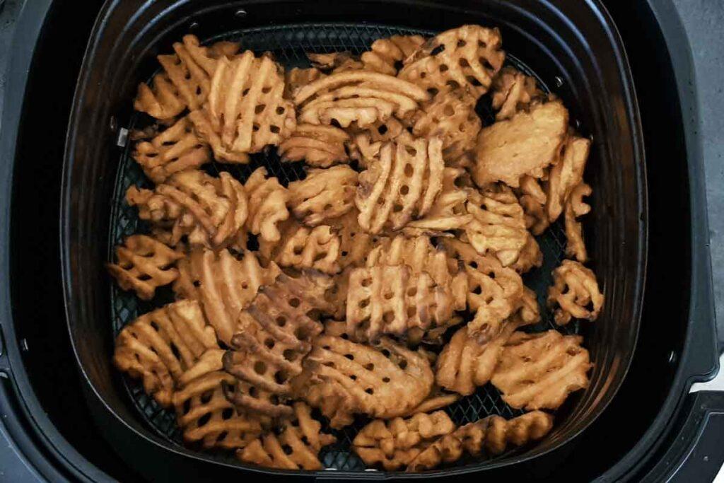 Air fried waffle fries in air fryer basket.