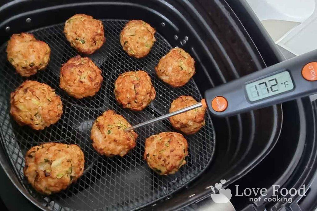 Cooked chicken meatballs in air fryer, instant-read thermometer reads 172F.