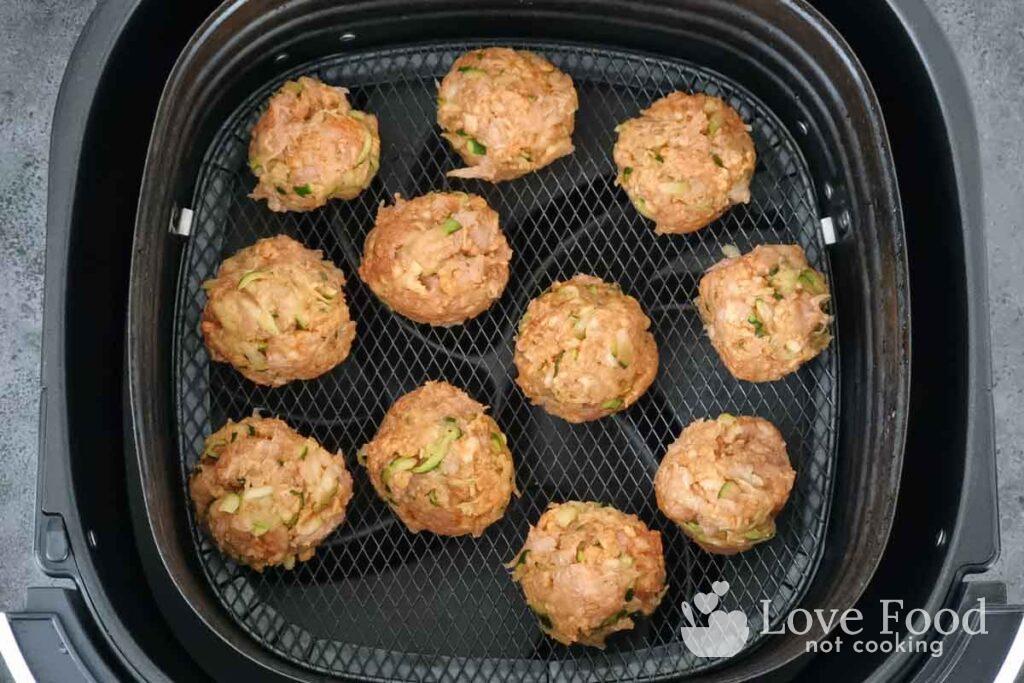Chicken meatballs in air fryer basket.