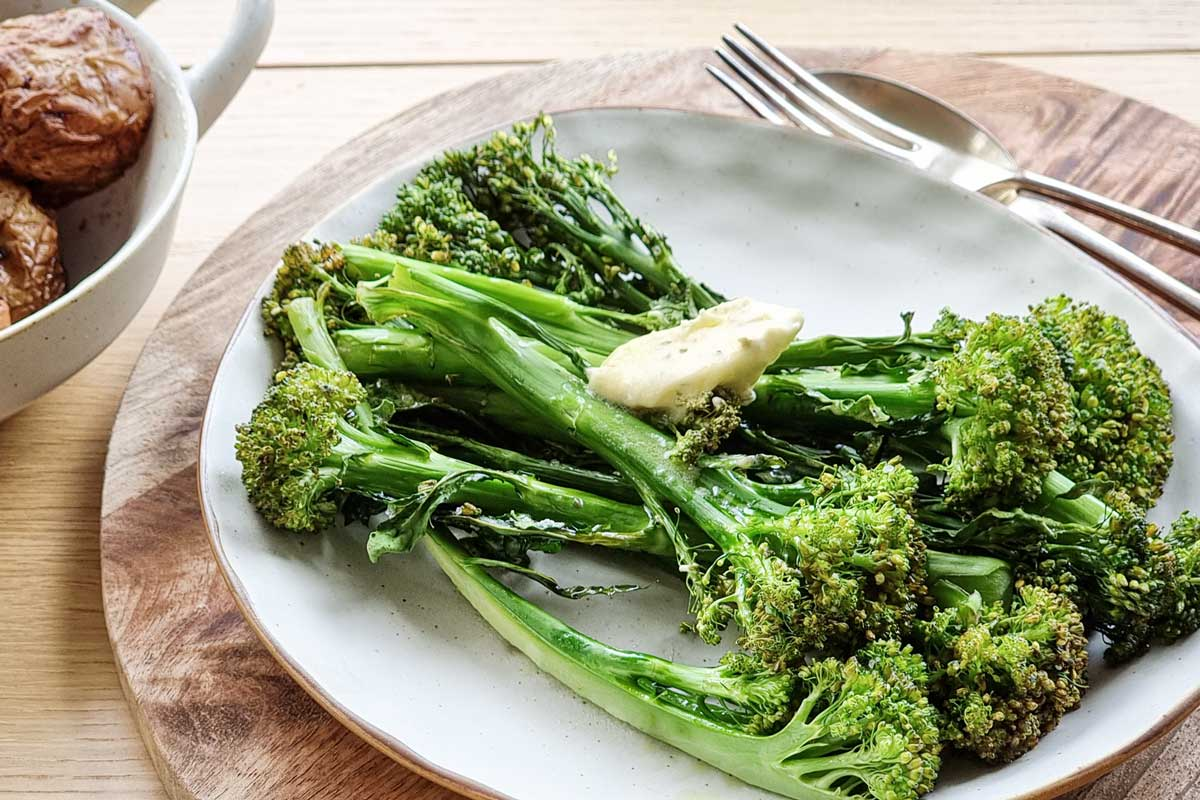 Air fried broccolini with garlic butter, on a white plate.