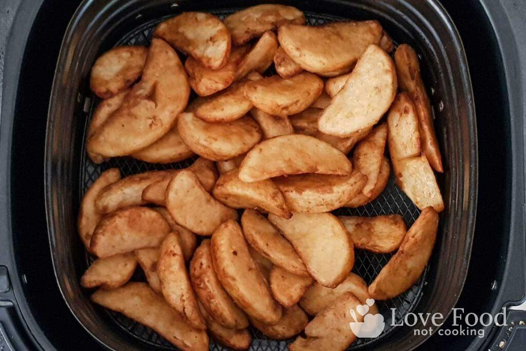 Air fried potato wedges in basket.