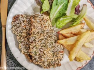 Air fryer beef schnitzel with fries and salad on a cream plate.