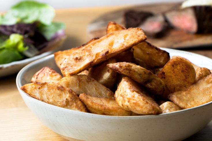 A grey bowl of air fried frozen potato wedges.