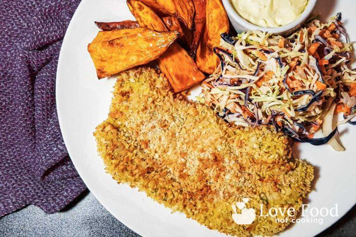 Air fryer pork schnitzel on a white plate with slaw and sweet potato fries.
