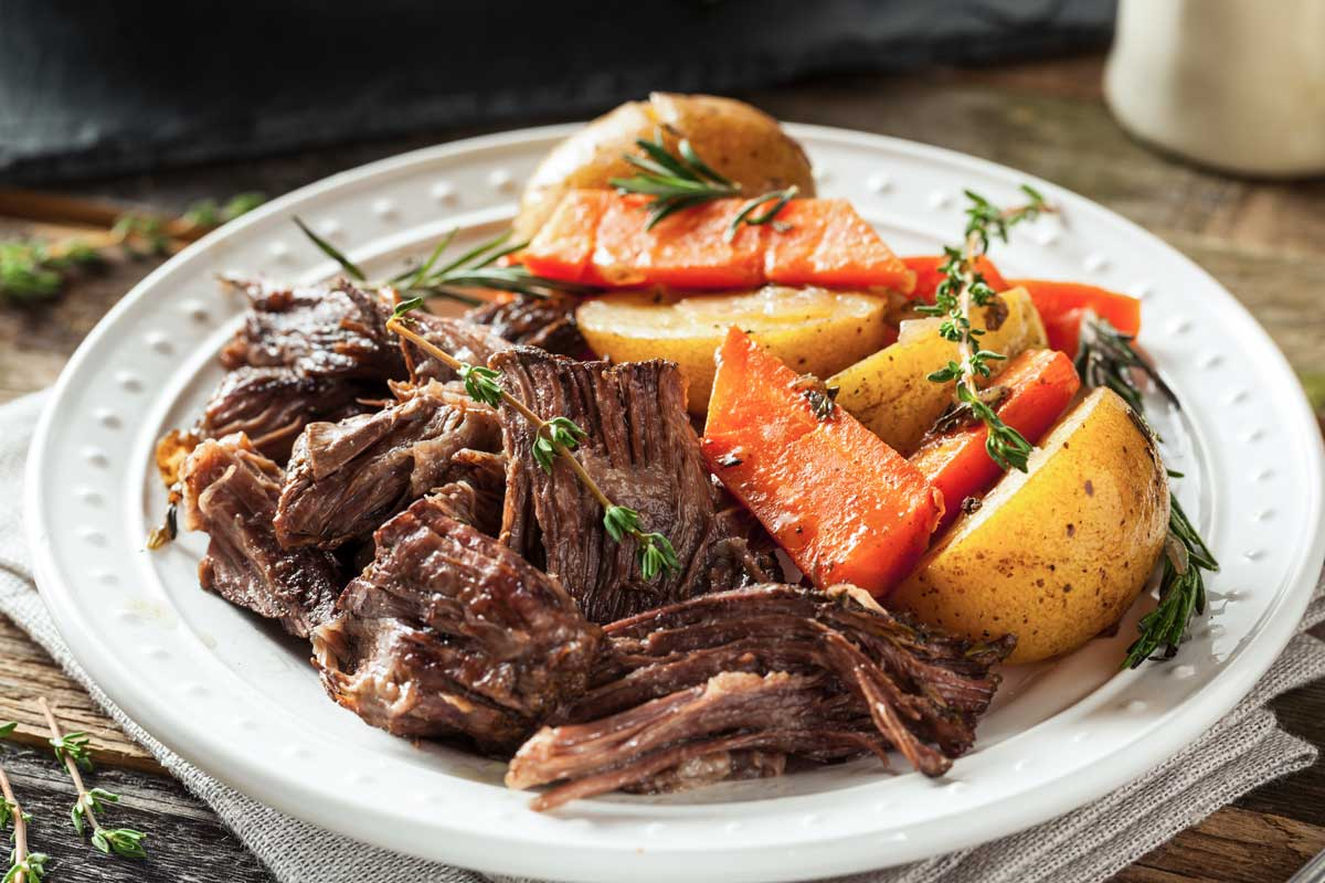Slow cooked beef pot roast on a white plate.