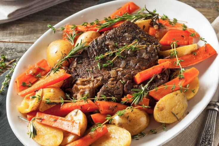 Beef pot roast with carrots and potatoes on a white plate.