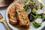 Air fryer pork steaks with a green side salad on a cream-colored plate.