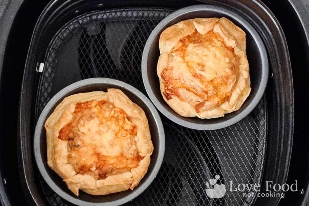 Cooked mini quiche in air fryer basket, golden brown and flakey.