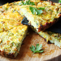 Air fryer frittata cut into slices on a wooden board.