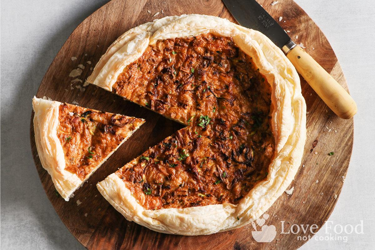 Top-down view of a quiche with a slice but from it.