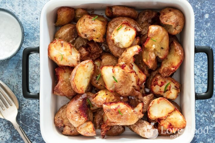 Air fryer smashed potatoes in a white serving dish.