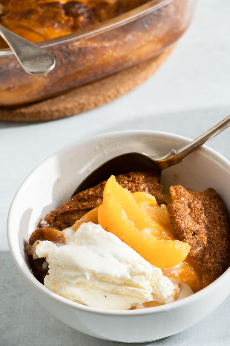 Side view of a bowl of peach cobbler topped with vanilla ice cream.