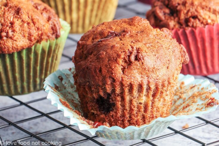 Air fryer banana muffins in colorful muffin cases on a black cooling rack.