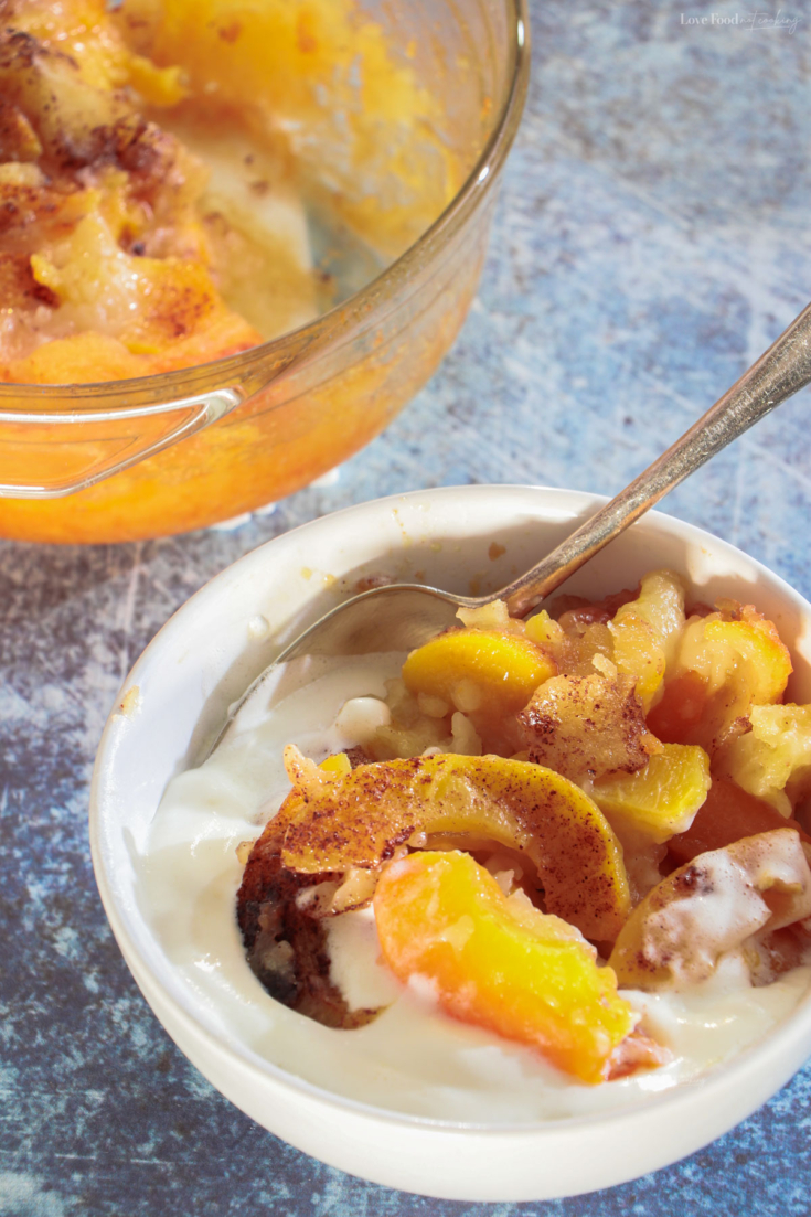 Peach cobbler in a serving dish and in a white bowl.
