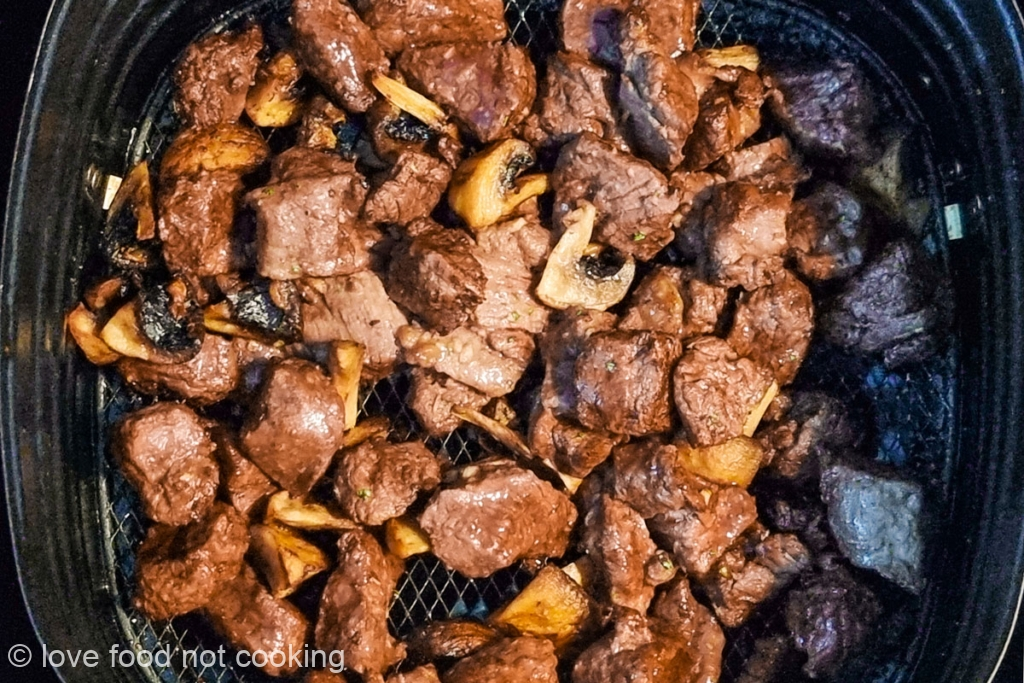 Cooked steak bites in air fryer basket.