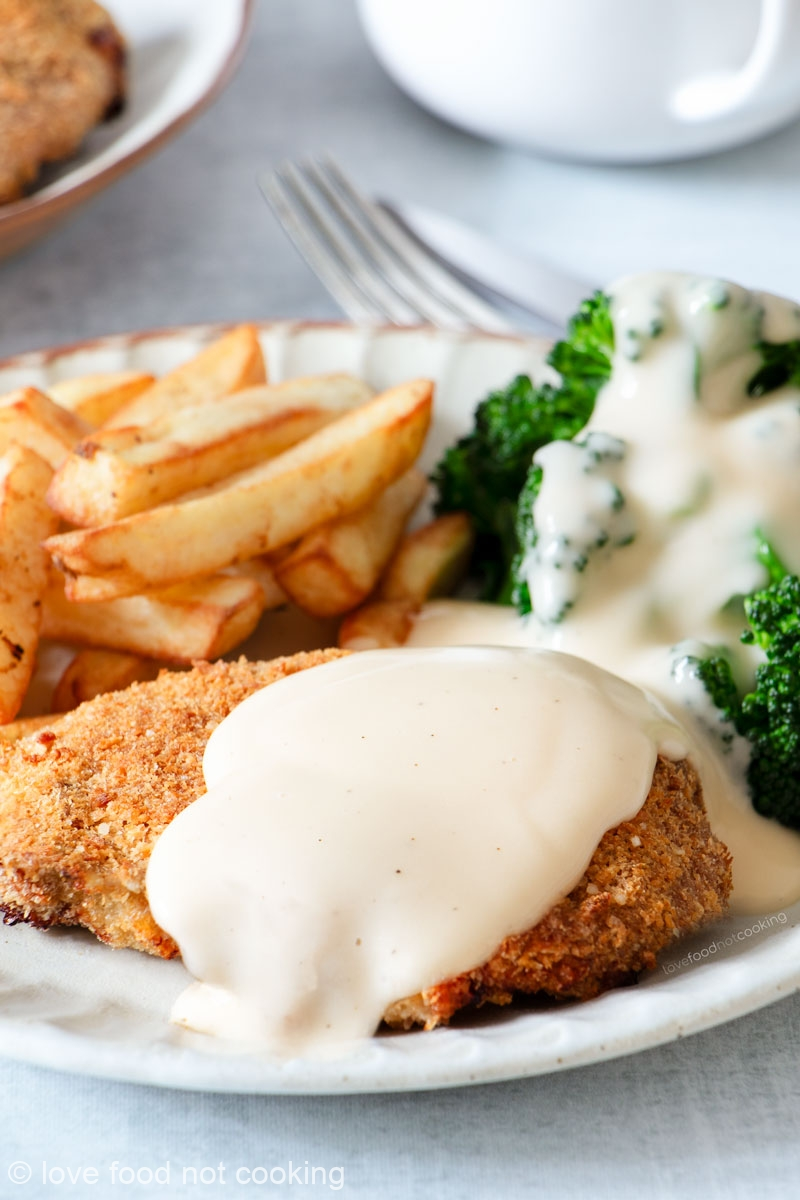 Air fryer chicken fried steak on a white plate with broccoli, fries and white gravy.