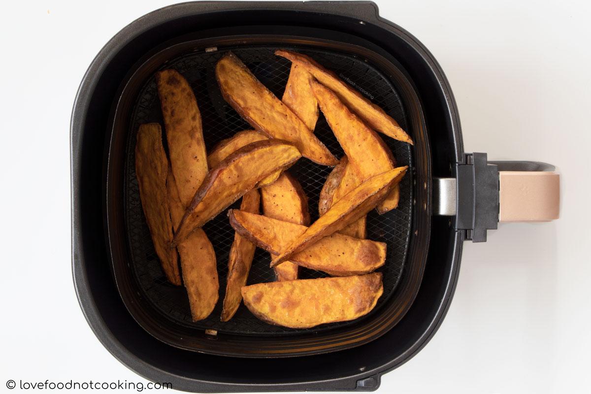 Air fried sweet potato wedges in air fryer basket.