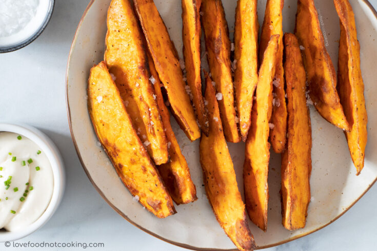 Air fryer sweet potato wedges on a white plate.