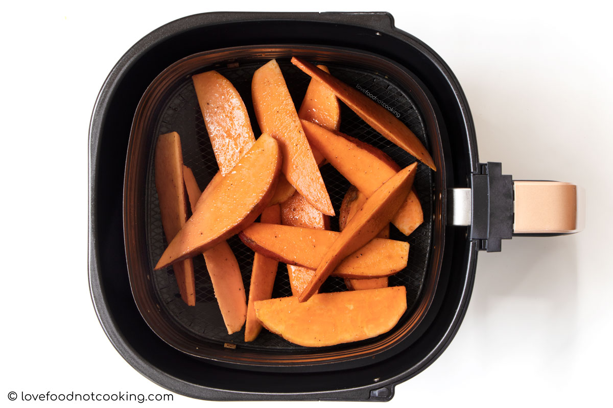 Sweet potato wedges in air fryer basket.
